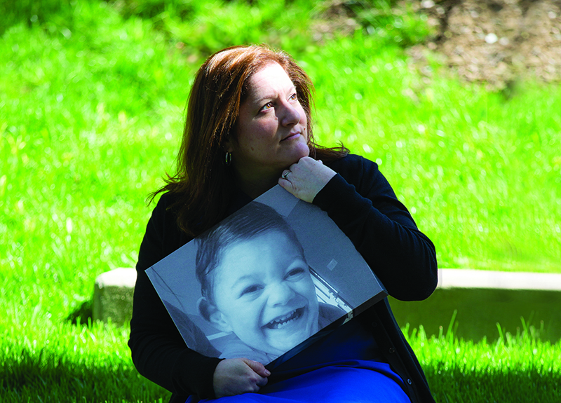 Stacy holds a photo of her son, Ryan