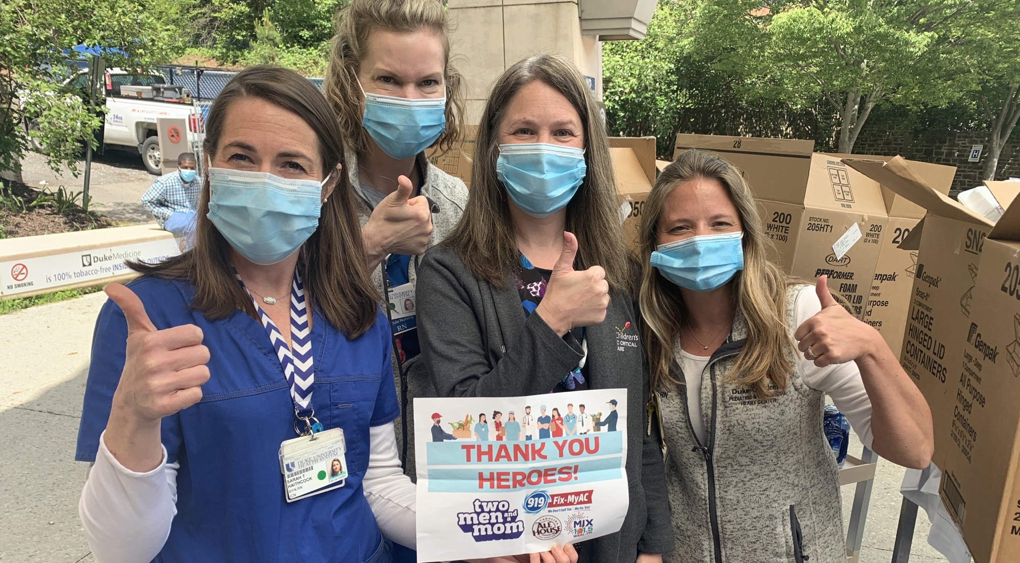 A group of masked nurses holding a sign give a thumbs up