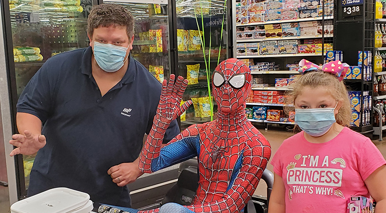 A Spider-Man and two shoppers wearing masks pose together