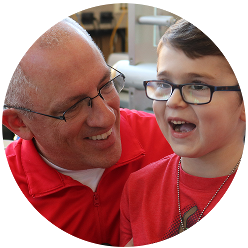 A man in a red shirt and glasses smiles at a little boy in a red shirt in glasses.