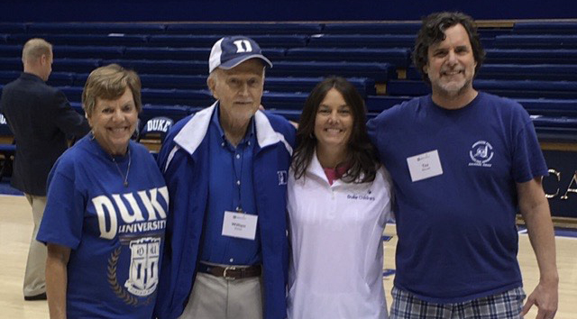 Four people stand in Cameron Indoor Stadium, Duke's Basketball Stadium: an older woman, an older man, a middle-aged woman, and a middle-aged man. All wear blue and white Duke athletics fan gear. The older man wears a baseball cap.