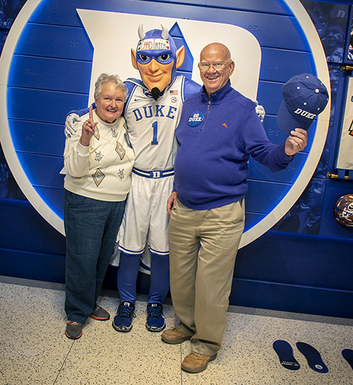 An elderly couple poses with the Duke Blue Devil