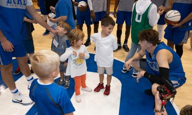 A Duke Men's Basketball player crouches and talks to a group of children.
