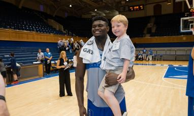 Zion Williamson, Duke Men's Basketball Player, holding a child on a basketball court.