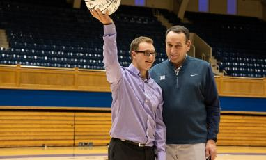 Coach K and a Duke Children's patient on the court at Cameron Indoor stadium.
