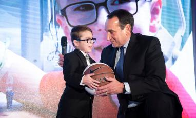 Coach K giving a basketball to a small child