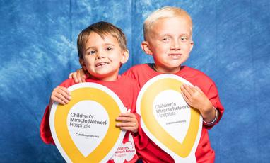 Two young boys holding CMN Hospitals Miracle Balloons