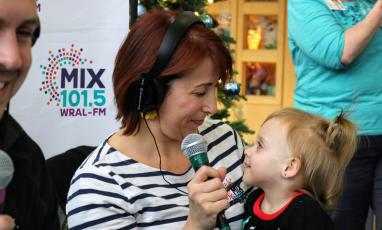 A woman wearing headphones and holding a microphone smiles down at a small child.